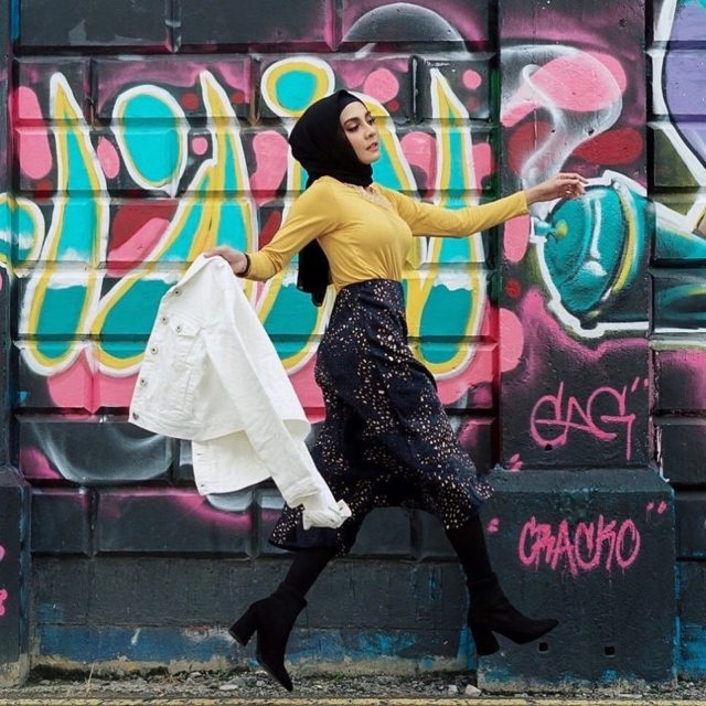 model in yellow top and black pants in front of a graffiti wall