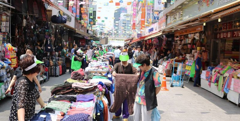 One of the Namdaemun Market streets selling clothing as visitors take a close look.