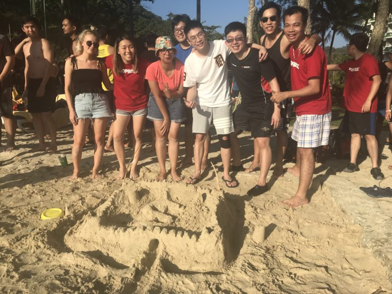 Shopback's team building a sand castle at the beach