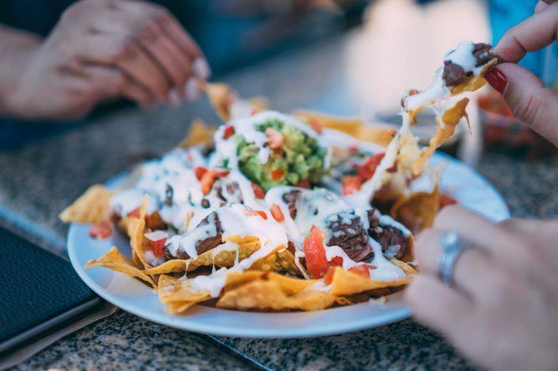 Friends enjoying a good plate of mexican loaded nachos in Singapore