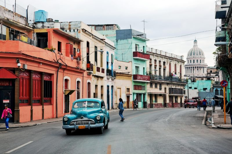 Old vintage blue car driving around Havana, Cuba