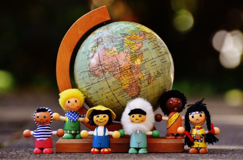 Toys of different nationalities with globe background