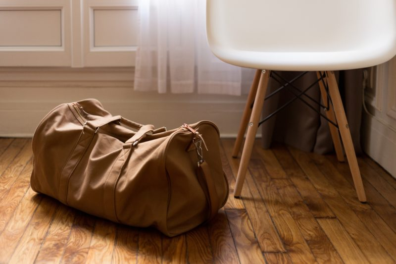 Brown duffle bag on floor next to chair