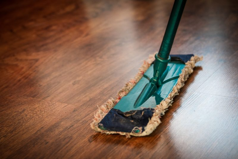 Cleaner mopping the wooden floor in apartment in Singapore