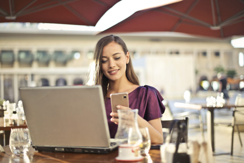 Similing woman working with laptop out of the office