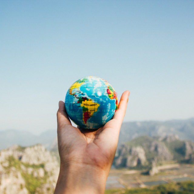 Hand holding out a small globe