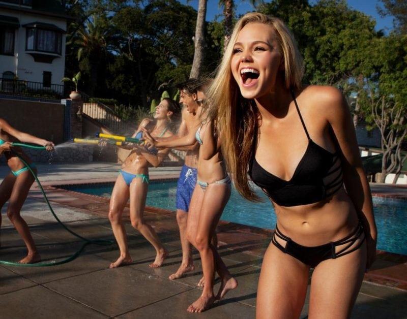 girl in bikini having fun at the pool with friends