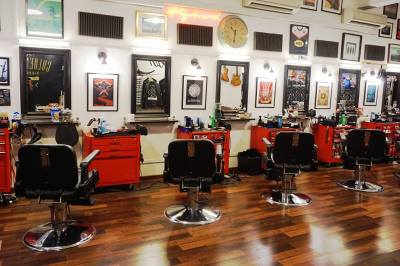 The Golden Rule Barber Co. Interiors with seats facing mirrors and decorated walls