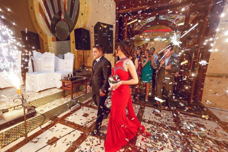 Happy married couple entering wedding reception venue