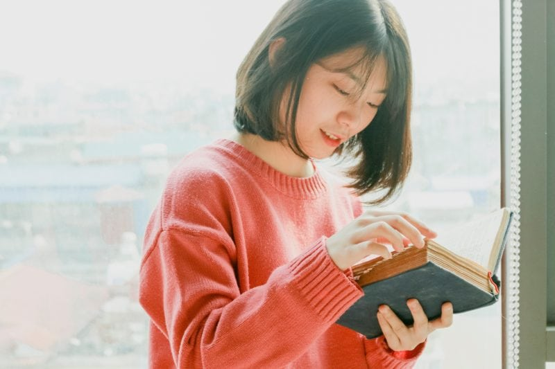 Girl in red reading a book