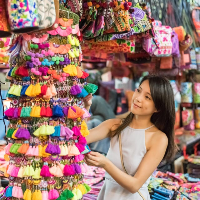 Singaporean girl shopping in street market in Bangkok