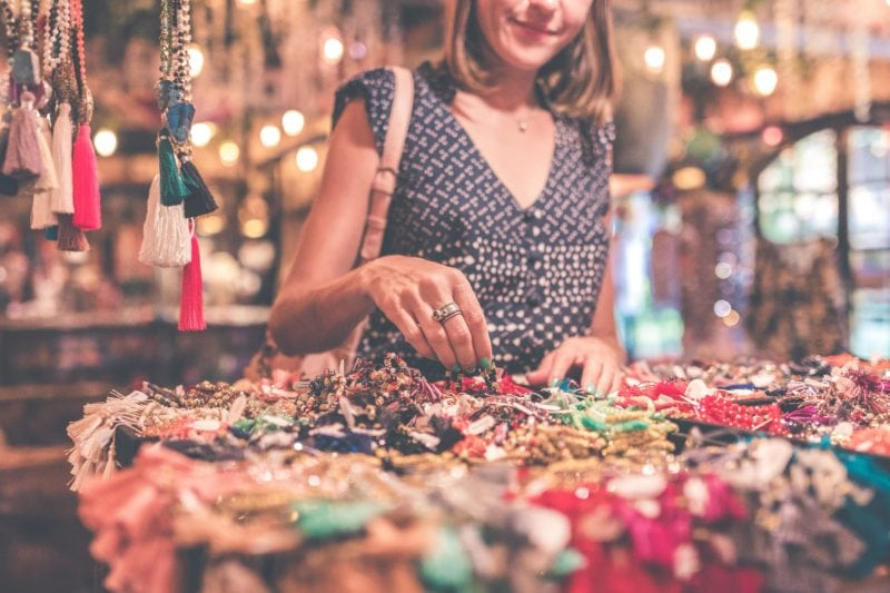 Girl buying fashion accessories at a market in bali