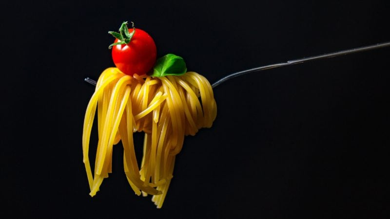 Pasta on fork with cherry tomato atop