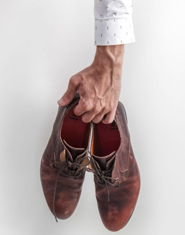 man holding quality worn dress shoes in singapore