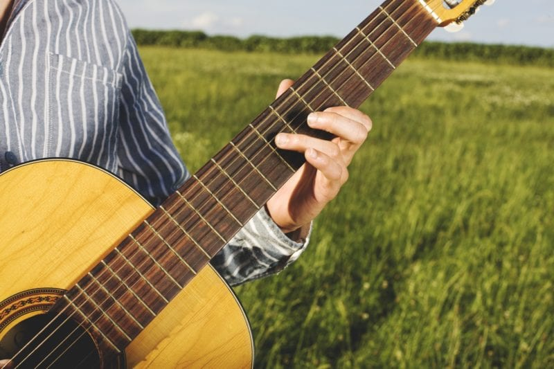 guitar held by hands with field backdrop