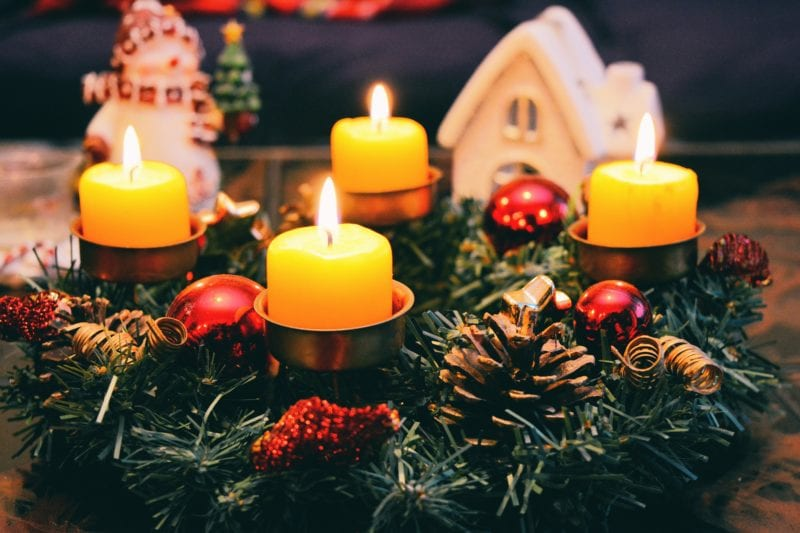 lighted candles in yellow on xmas deco