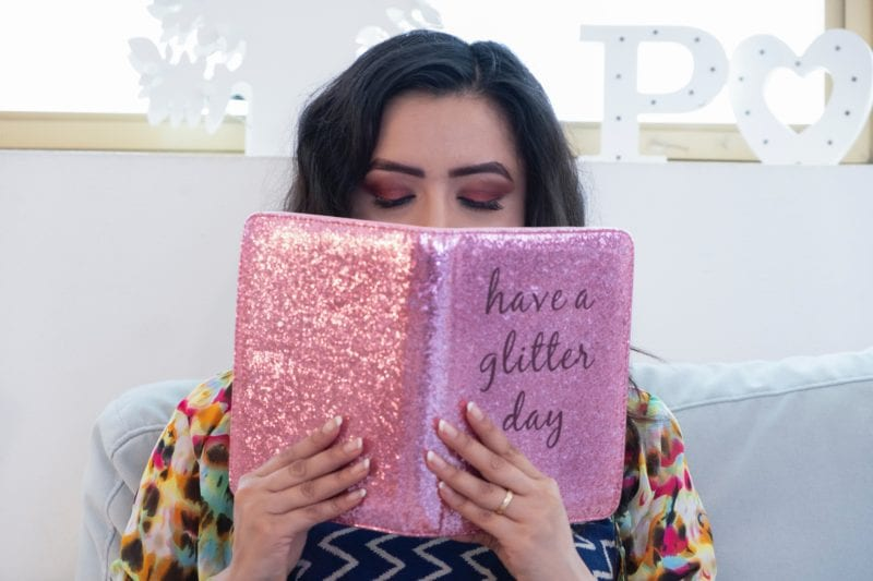 lady holding a pink glitter journal
