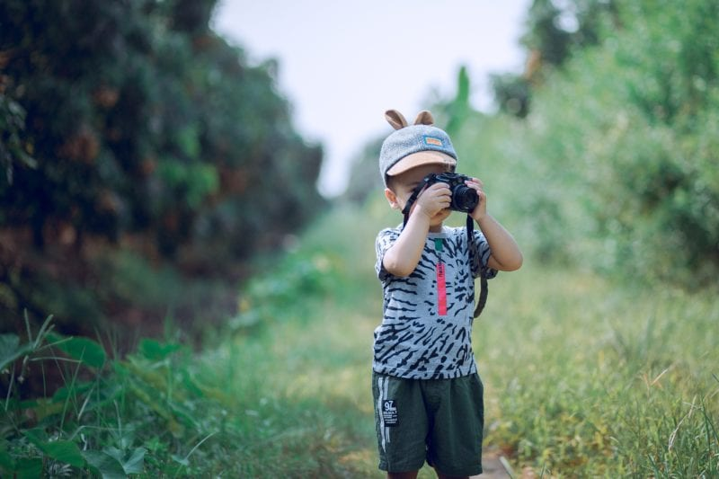 kid holding mini camera with nature as backdrop