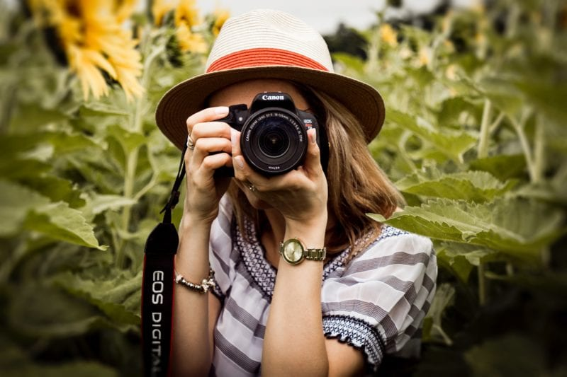 Lady holding Canon EOS camera to aim and shoot with nature backdrop