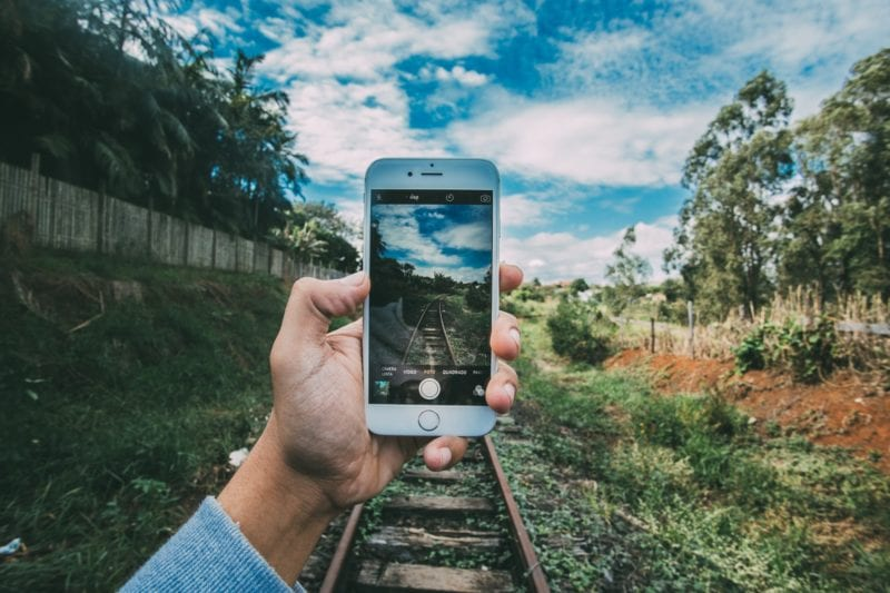 Hand holding iPhone with railway track and trees in background