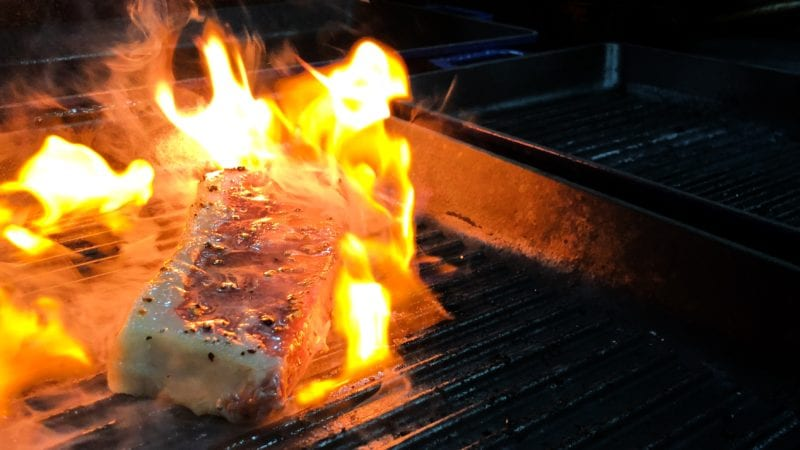 Meat on grill aflame