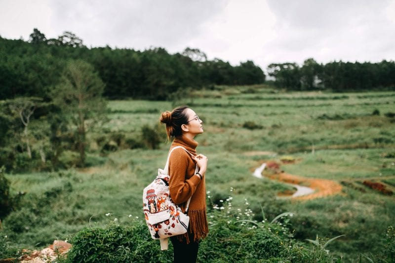 girl in brown top with backpack standing against nature backdrop