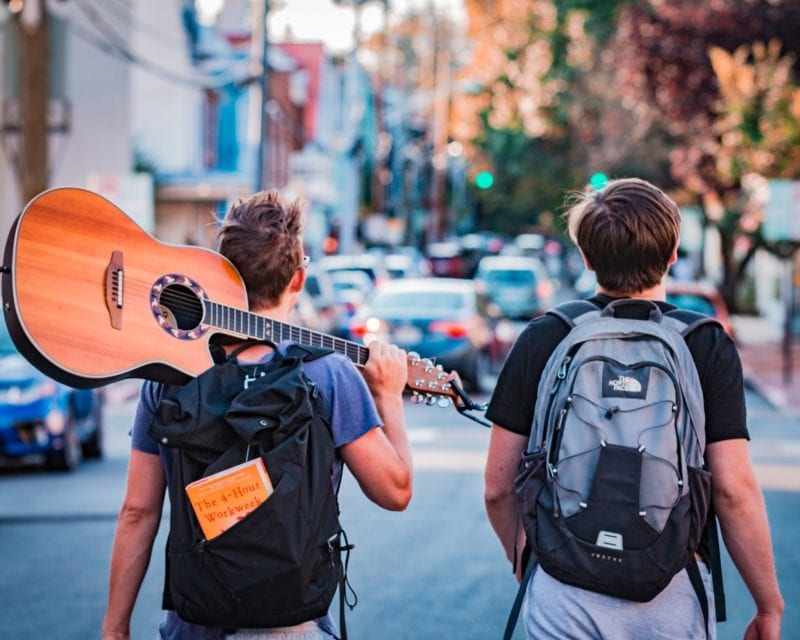 2 backpackers on the street - one with guitar