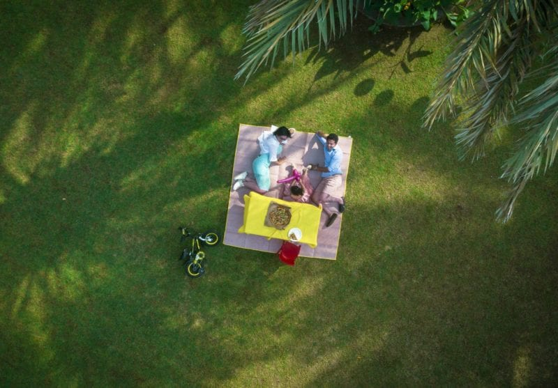 aerial view of couple on greens with picnic basket