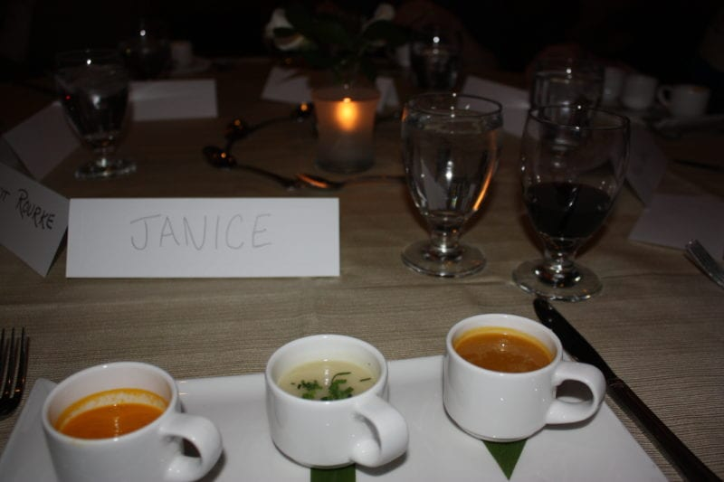 dining in the dark table setup with cups of soup and drink glasses