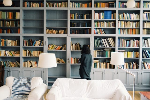 woman looking at books on bookshelves