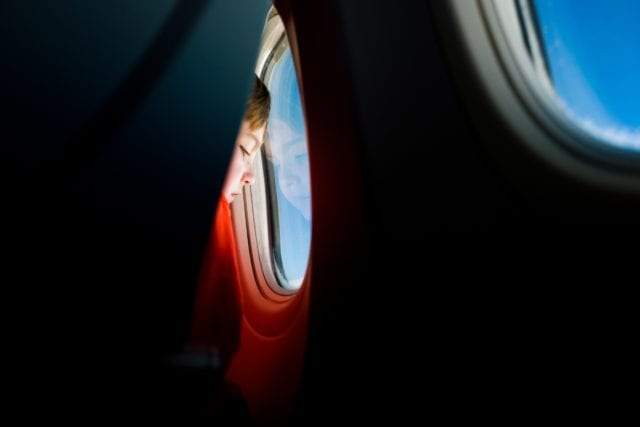 boy on plane seat looking out window