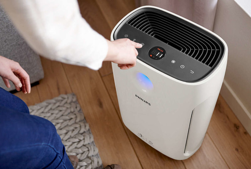 woman pressing the controls on an air purifier