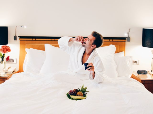 man eating fruit in hotel bed