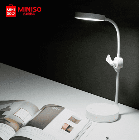 desk lamp with mini fan on table with magazine