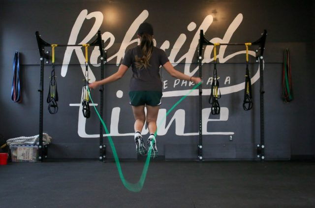 woman jumping rope in gym with graffiti background