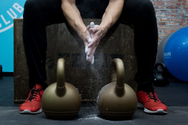 two kettlebells in front of a man