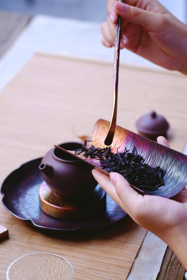 man scooping tea leaves into tea pot