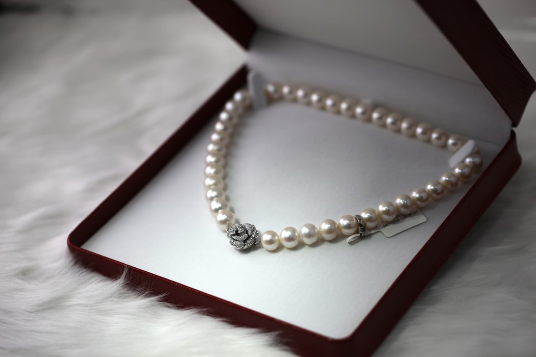 string of pearl necklace with diamond center in box