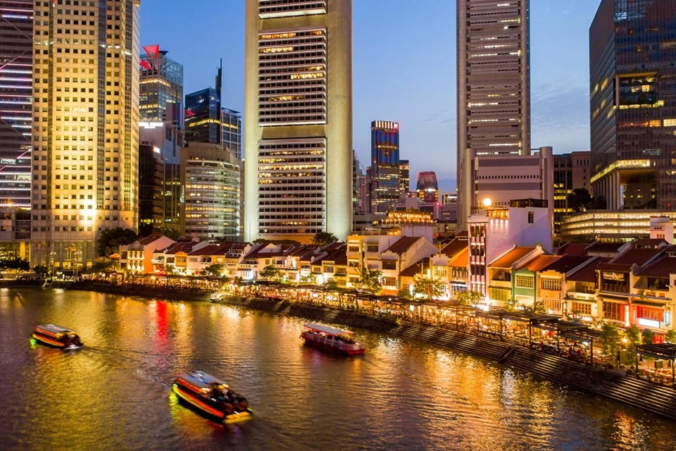 two boats cruising along a river at night with shophouses and buildings