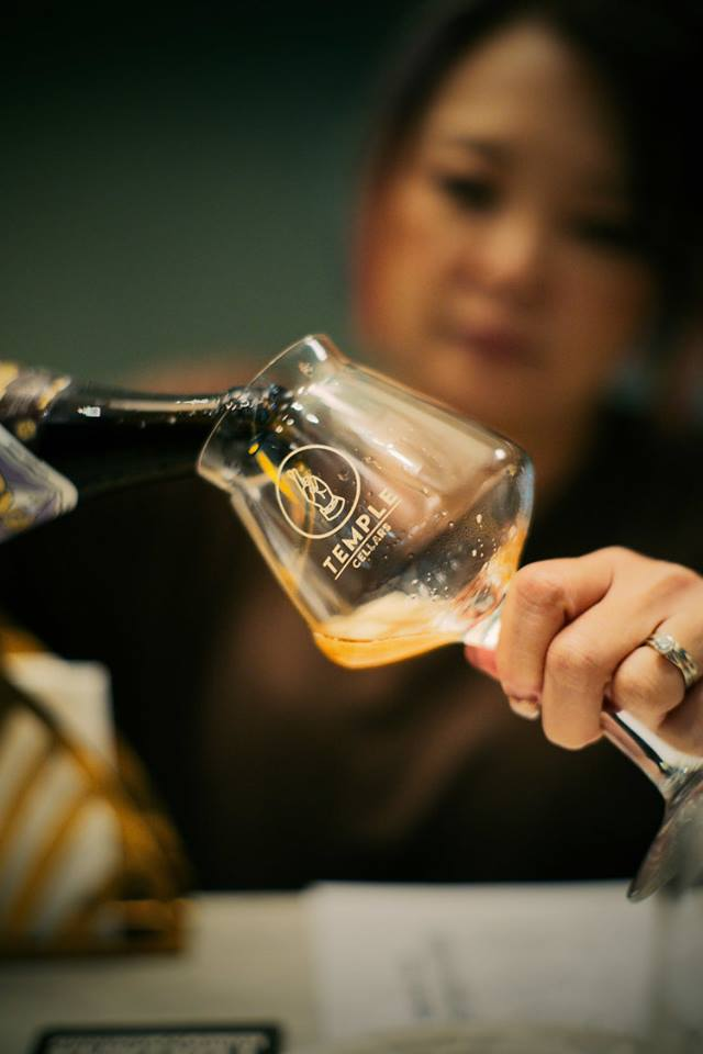 woman pouring beer into glass cup
