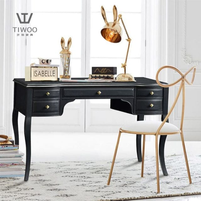 gold frame ribbon designed chair with black wooden table and rabbit ears table lamp