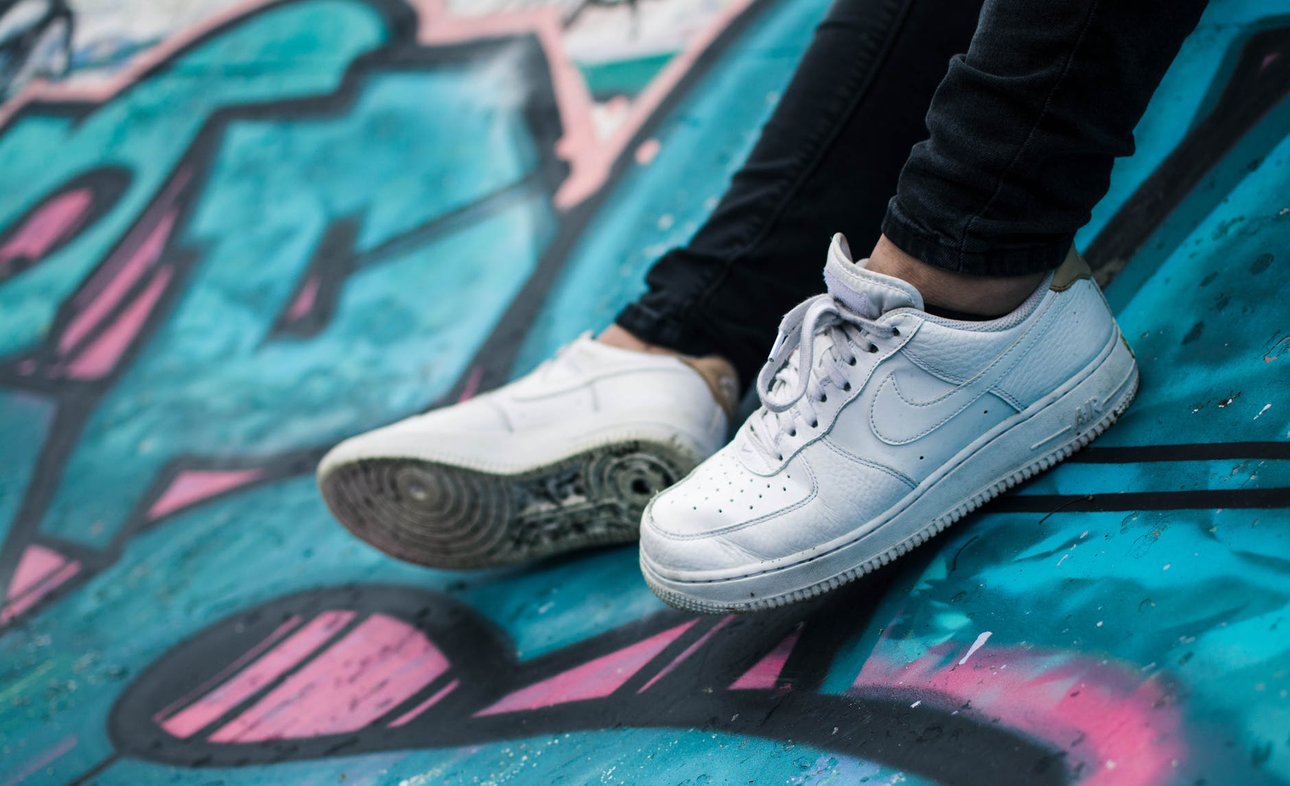 white sneakers on blue and pink graffiti wall