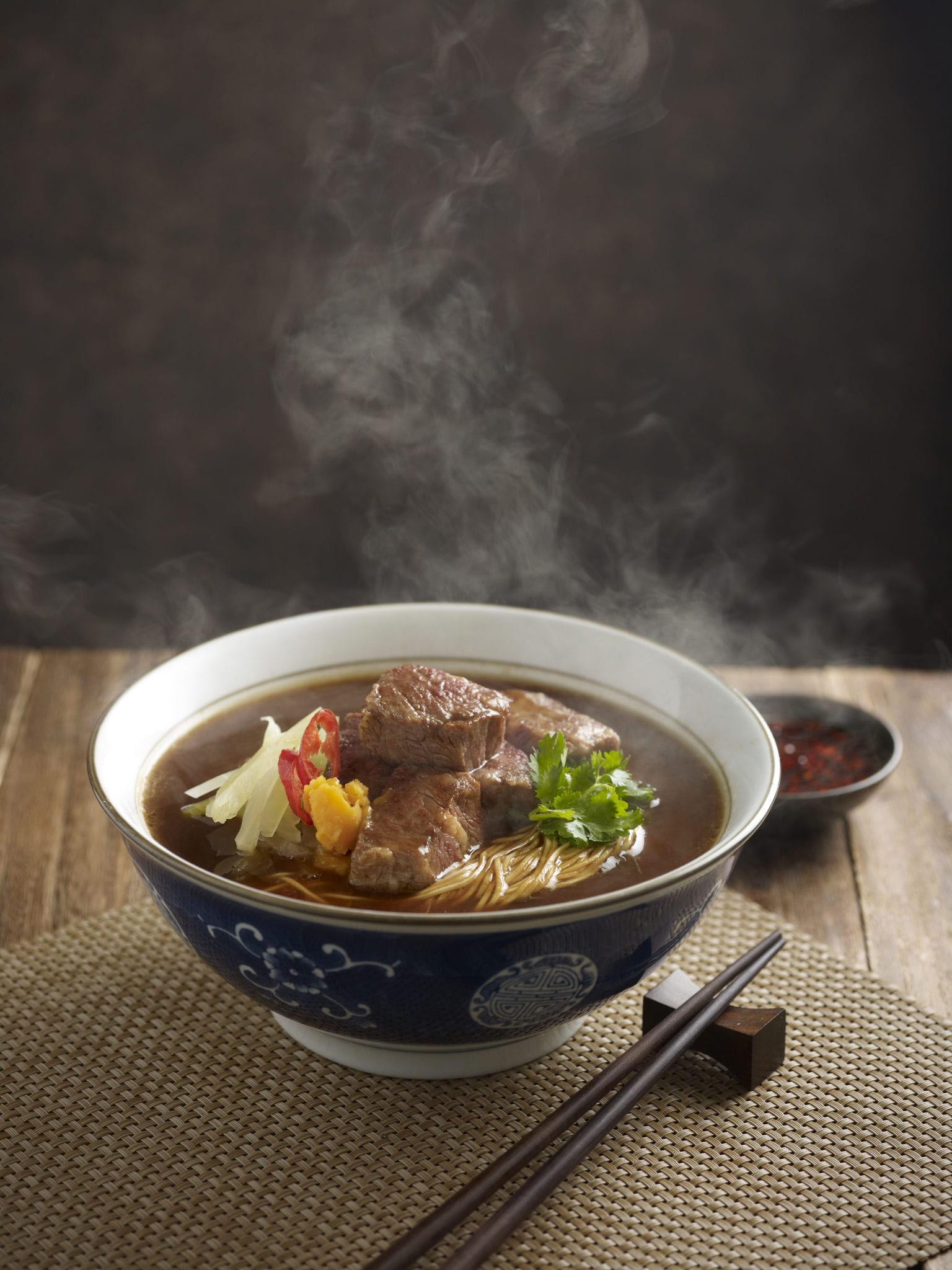 hot bowl of noodles with beef broth and beef cud's