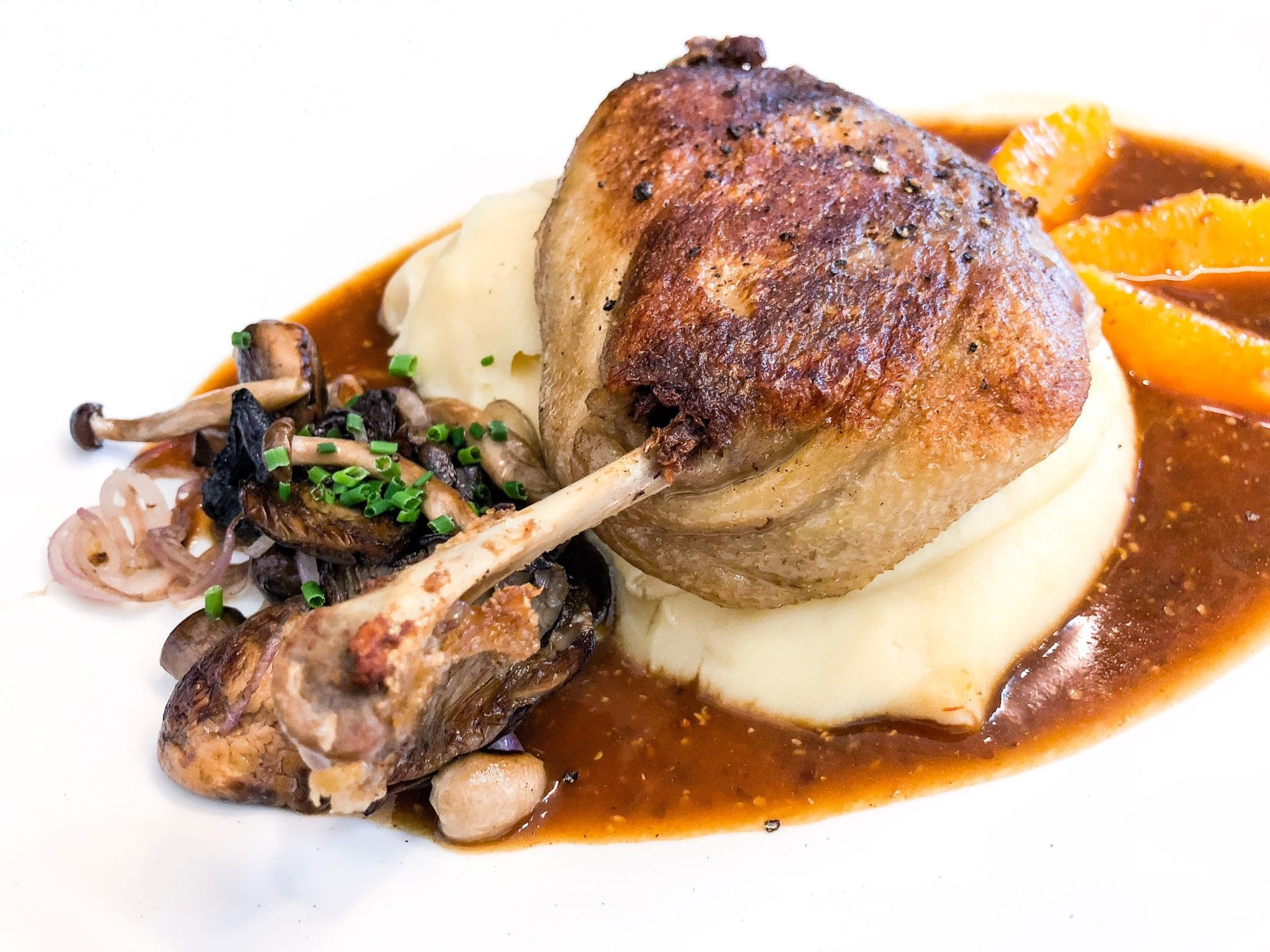 duck confit with sauce on mash potatoes
