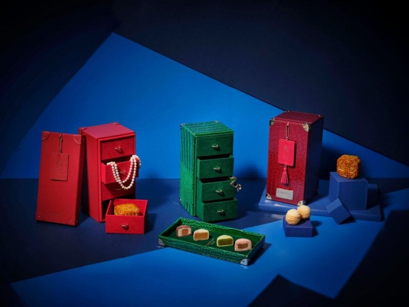 two red boxes and one green box of mooncake that works as jewellery case
