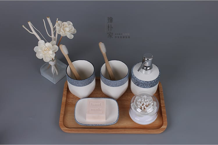 white and grey ceramic bathroom set with dried white flowers and soap bar