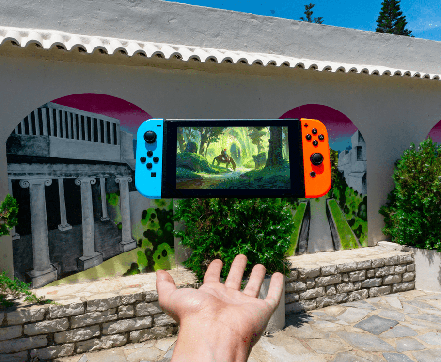nintendo switch with game floating above human palm