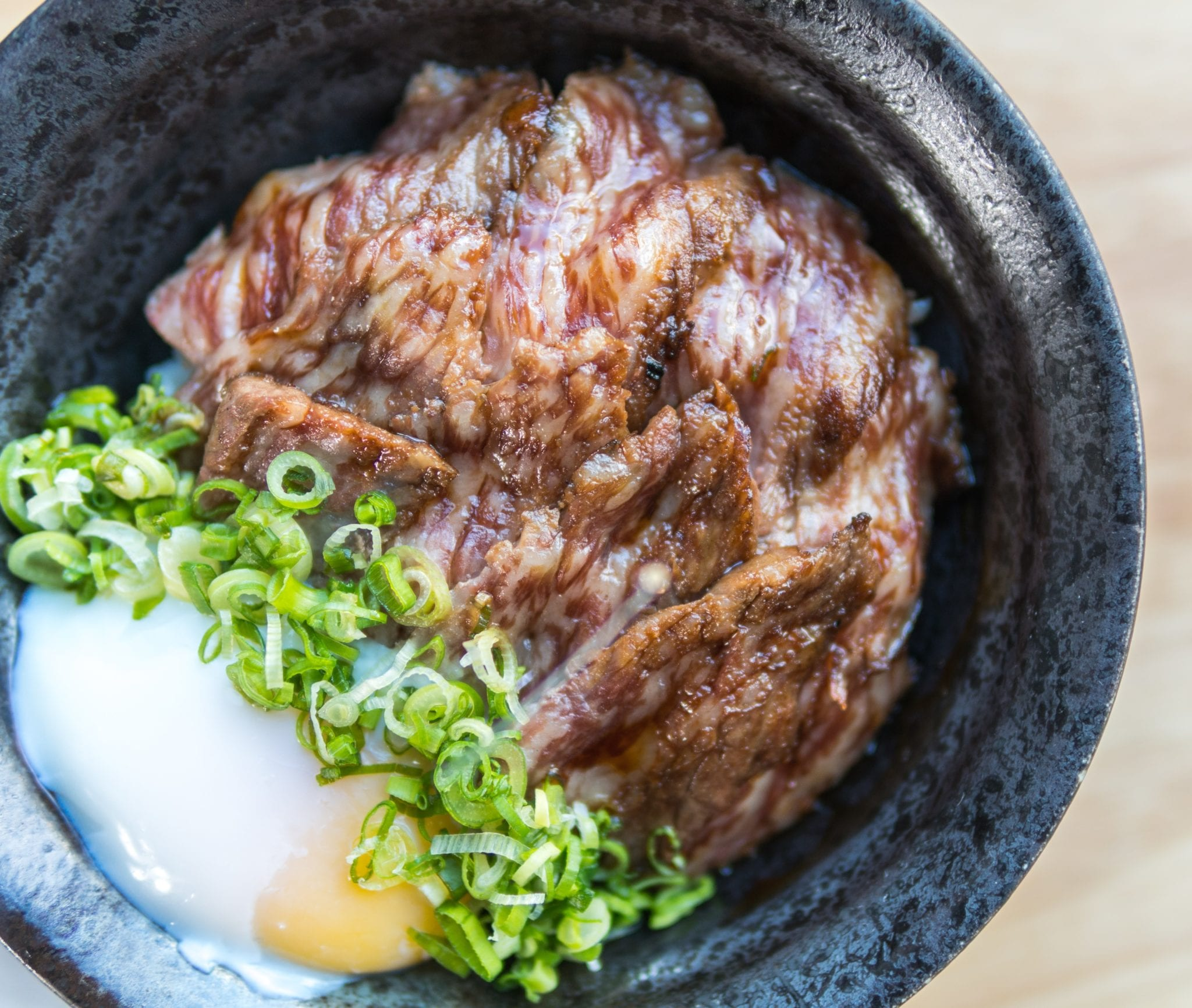 seared wagyu beef with chives and onset egg