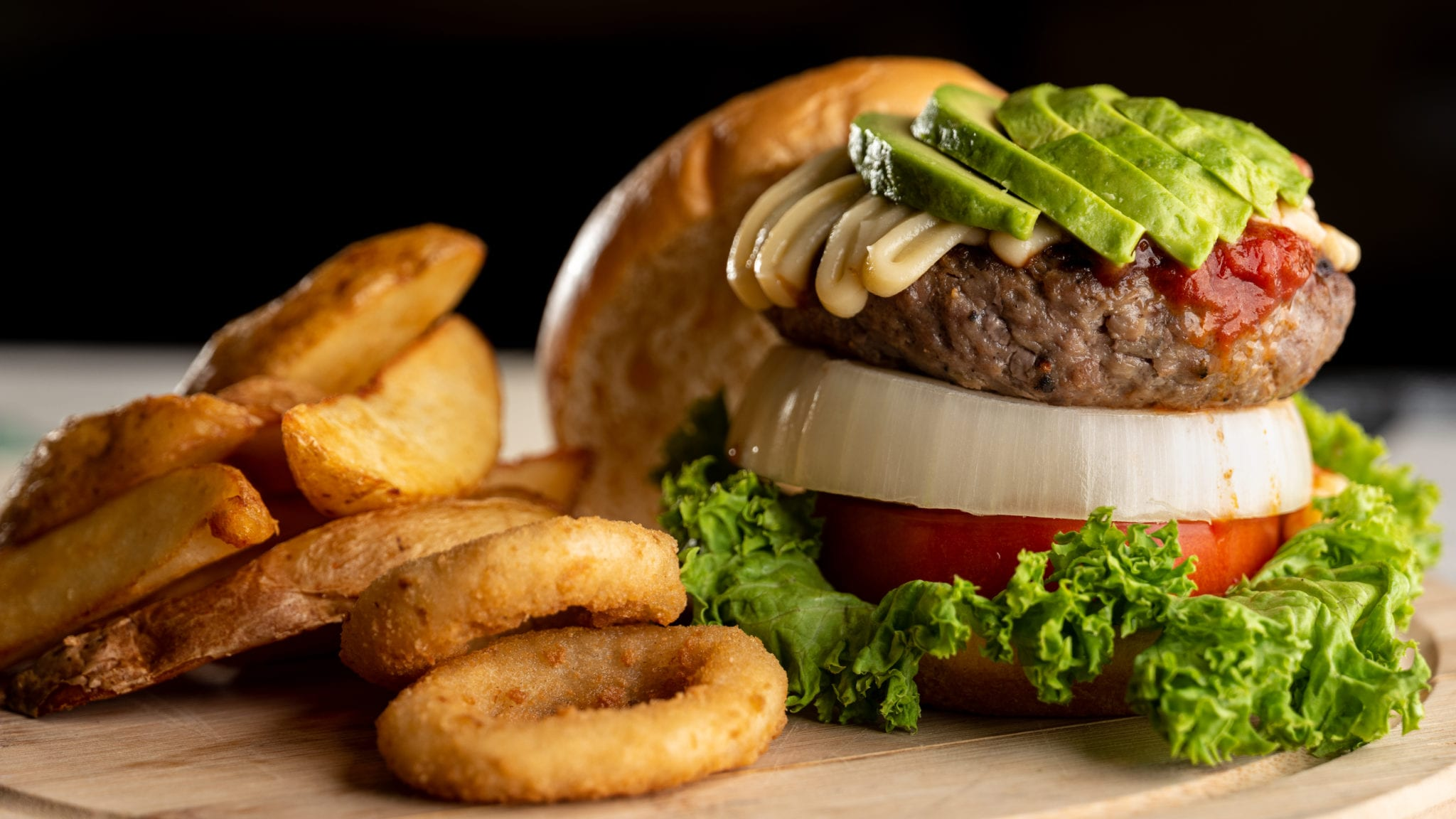 wagyu beef burger with lettuce, tomatoes, onions, avocados and onion rings