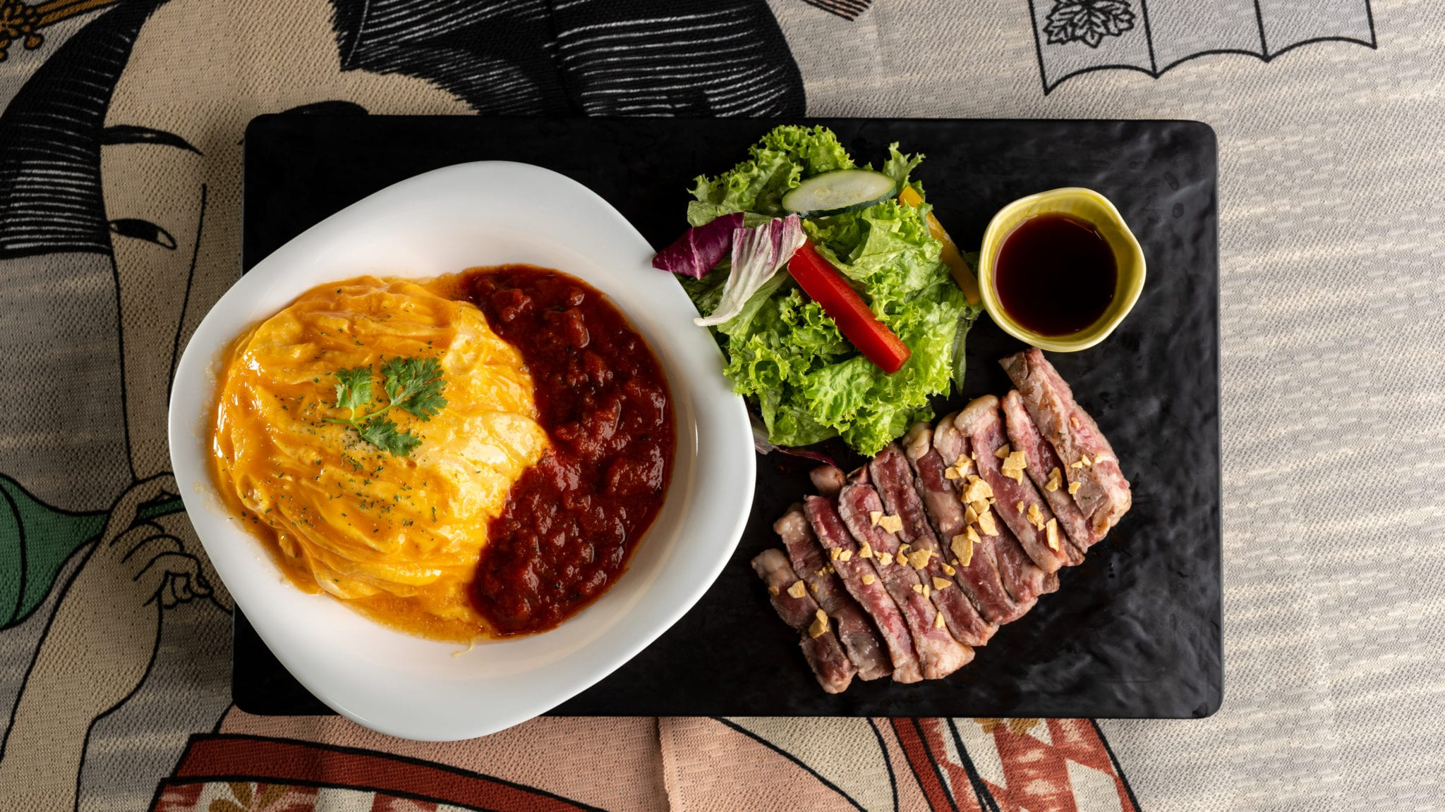 omelette on rice with sauce and steak and salad